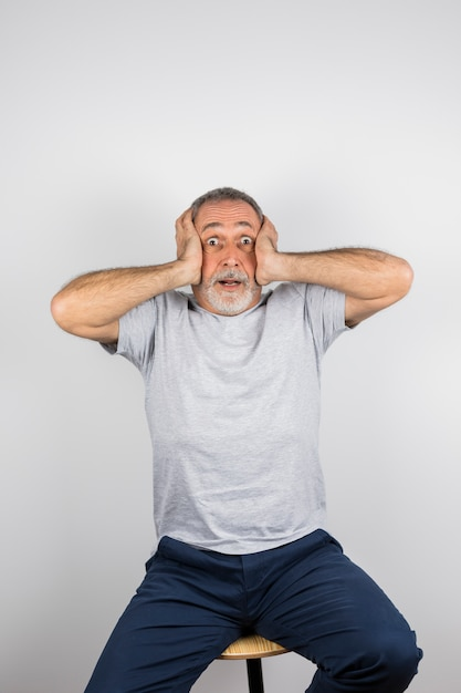 Aged amazed man with hands on head on chair Free Photo