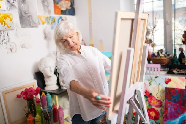Aged artist. aged artist with short blonde hair wearing white blouse standing near drawing easel Premium Photo