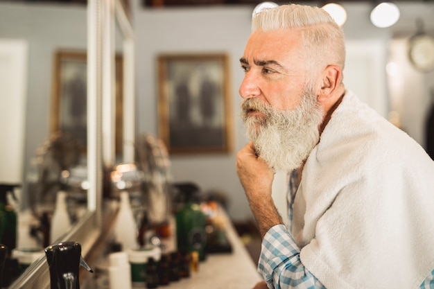 Aged client evaluating work of hairdresser in barbershop Free Photo