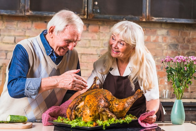 Aged couple cooking turkey in kitchen Free Photo