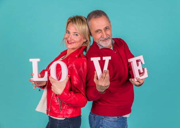 Aged couple showing love inscription Free Photo