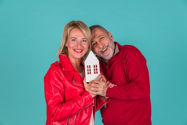 Aged couple showing toy house Free Photo