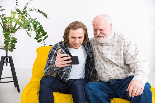 Aged father browsing smartphone with young son Free Photo