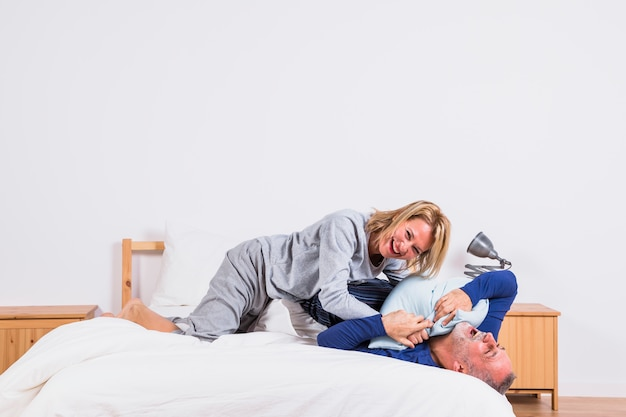 Aged happy woman and man having fun with pillows and lying on bed Free Photo