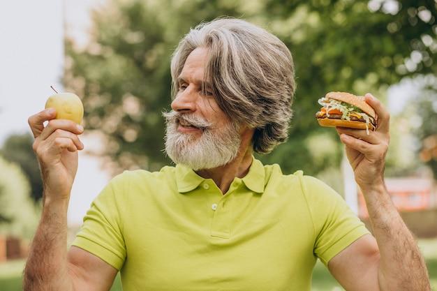 Пожилой мужчина, выбирая между гамбургером и яблоком Бесплатные Фотографии