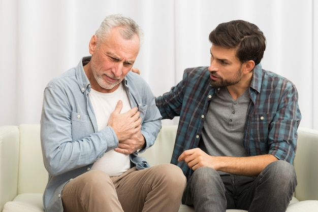 Aged man having heart attack near young guy on sofa Free Photo