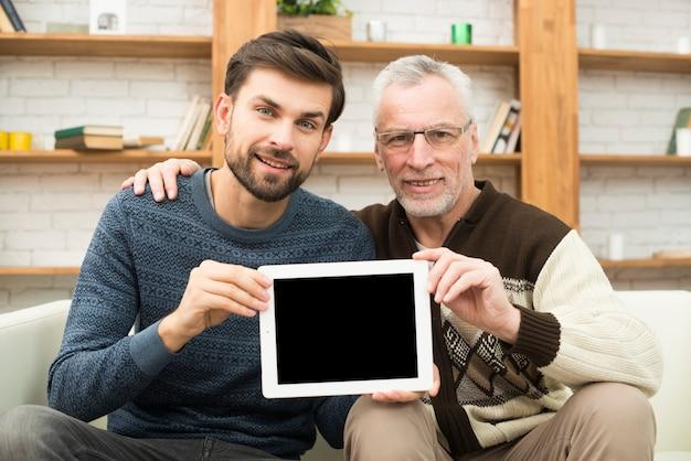 세 남자 포옹 젊은 남자와 긴의 자에 태블릿을 보여주는 무료 사진