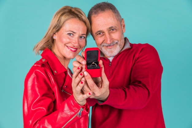Aged man and positive woman showing jewellery box Free Photo