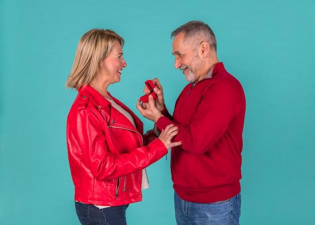 Aged man presenting jewellery box to amazed woman Free Photo