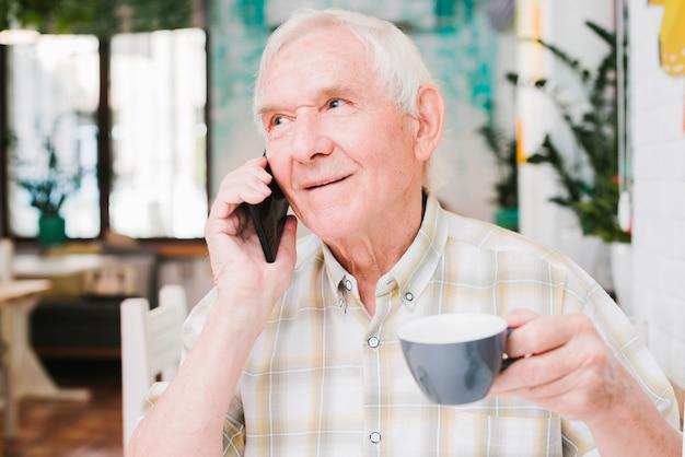 カップを手に電話で話している高齢者の男 無料写真