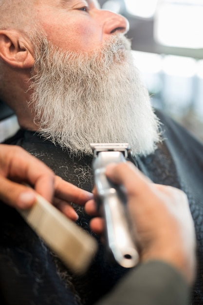 Aged man with long gray beard in barbershop for trimming Free Photo