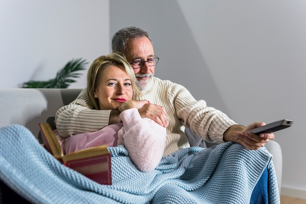 Aged man with tv remote watching tv and smiling woman with book on sofa Free Photo