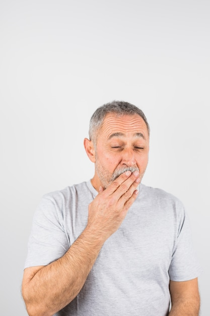 Aged man yawning covering  his mouth Free Photo
