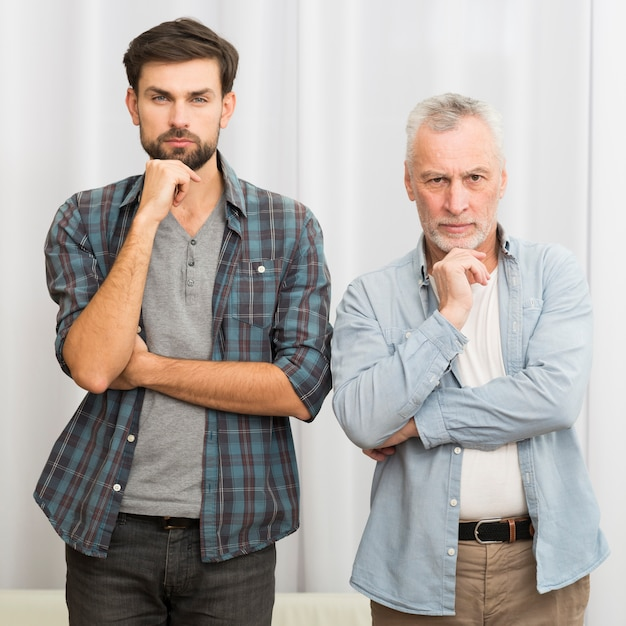 Aged man and young guy with hands near chins Free Photo