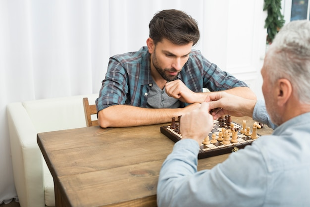 Aged man and young pensive guy playing chess at table in room Free Photo