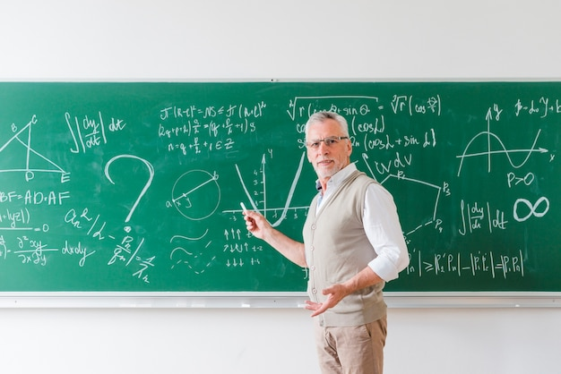 Aged math teacher pointing with chalk at blackboard Free Photo