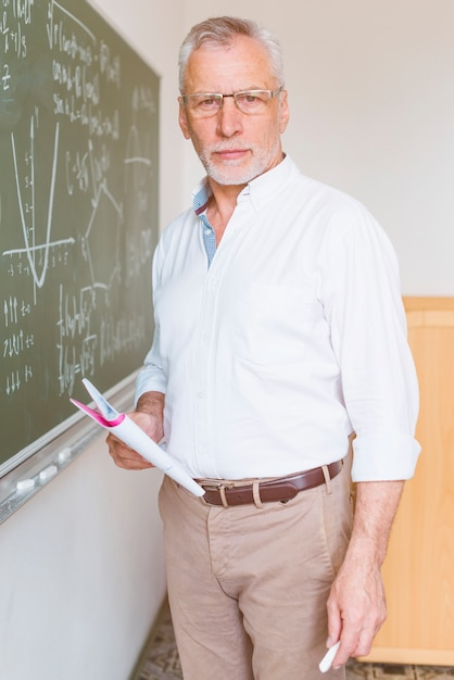 Aged math teacher standing in classroom with chalk Free Photo
