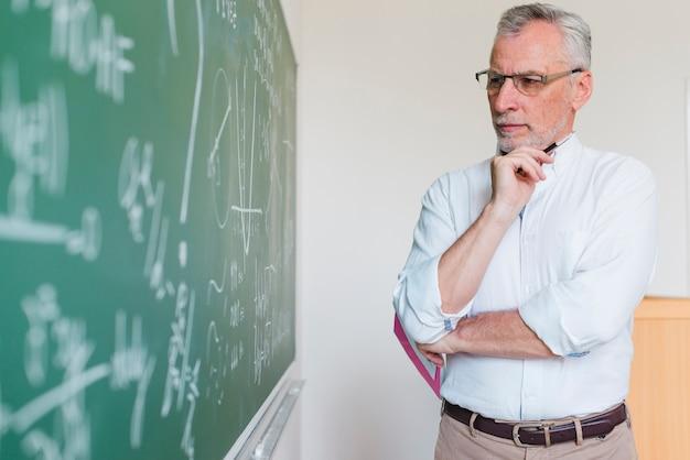 Aged math teacher thinking next to chalkboard Free Photo