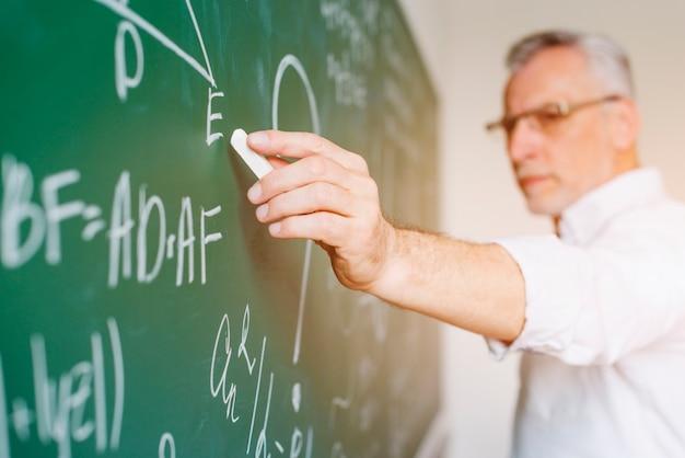 Aged math teacher writing on chalkboard Premium Photo