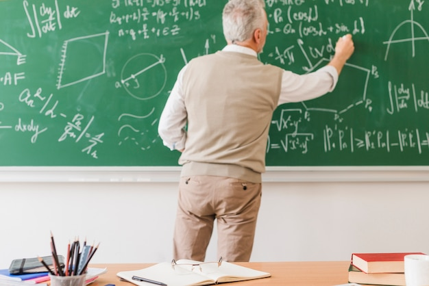 Aged math teacher writing equation on chalkboard Free Photo
