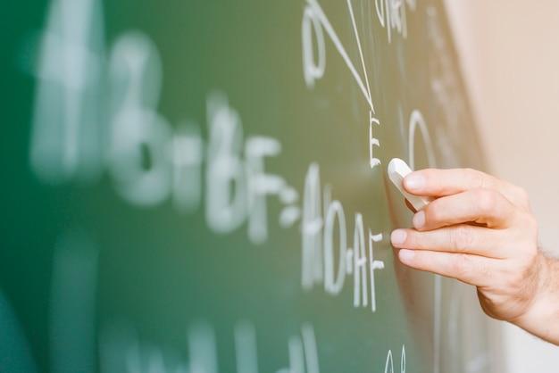 Пожилой учитель математики, написание формулы на доске Premium Фотографии
