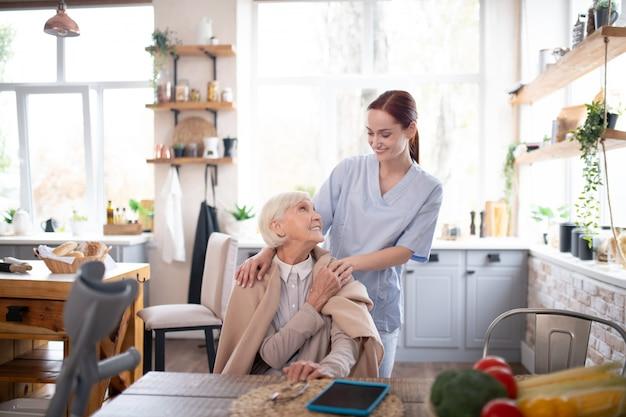 Aged pensioner feeling thankful to her pleasant caregiver Premium Photo