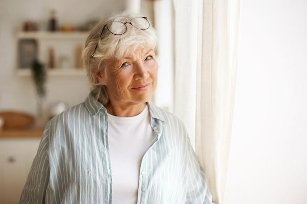 Пожилые люди, зрелость, пенсия и концепция образа жизни. внутреннее изображение небрежно одетой пожилой зрелой женщины с седыми волосами, стоящей у окна, в очках на голове и ощущающей себя одинокой Бесплатные Фотографии