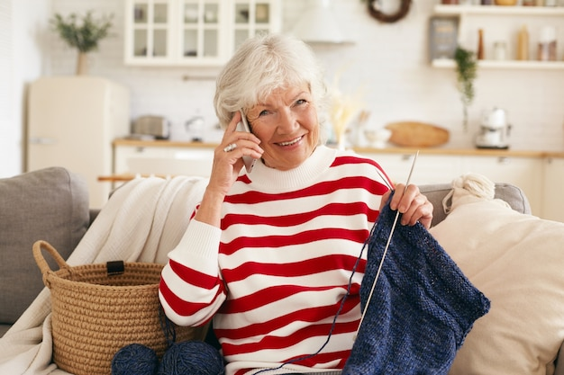 Aged people, retirement, leisure and modern technology concept. beautiful happy grandma with gray hair talking to her granddaughter on mobile phone while knitting scarf on couch in living room Free Photo