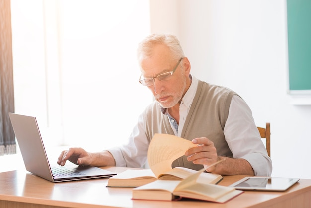 Aged professor male working with laptop while reading book in classroom Free Photo