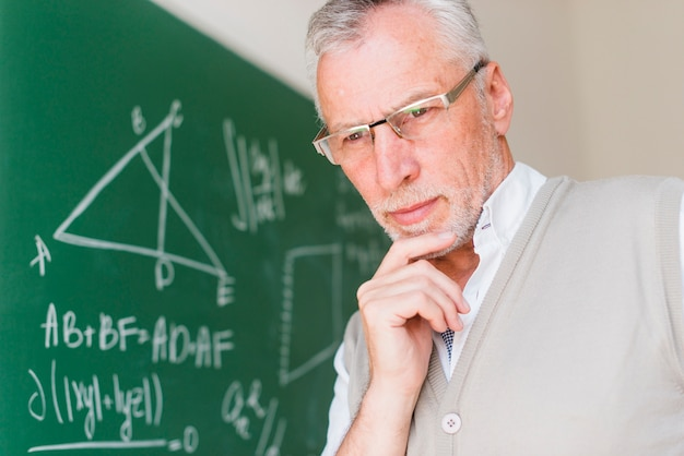 Aged professor standing near chalkboard in classroom Free Photo