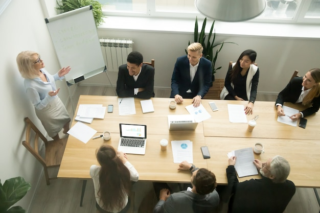 Aged senior businesswoman giving presentation at multiracial group office meeting Free Photo