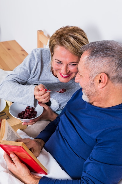 Aged smiling woman giving berries to man with book on bed Free Photo