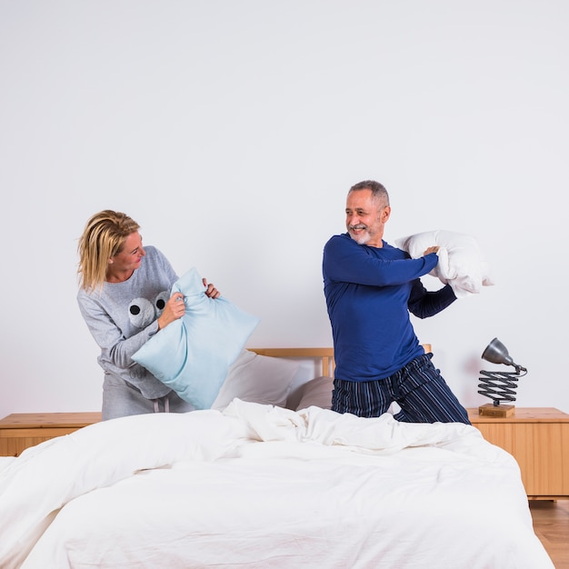 Aged smiling woman and man with pillows having fun on bed Free Photo
