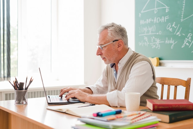 Aged teacher working at laptop in classroom Free Photo