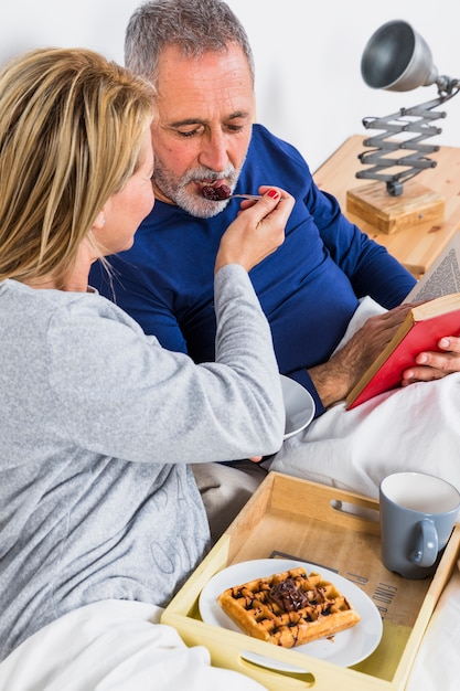 Aged woman giving berries to man with book near tray with breakfast on bed Free Photo