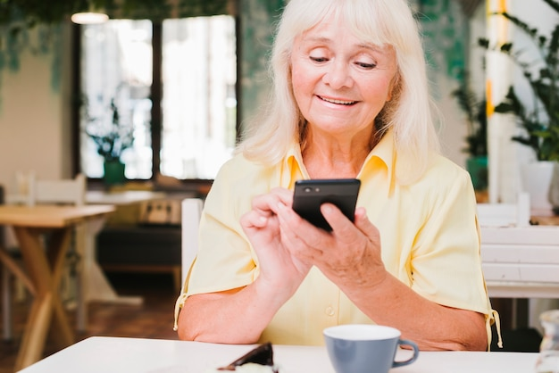 Aged woman using smartphone at home Free Photo