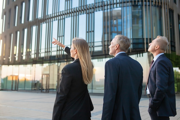 Agent and customers meeting outdoors, discussing real property, pointing at office building. back view. commercial real estate concept Free Photo