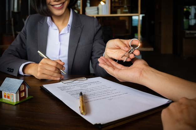Agents are giving house keys of customer after sign agreement contract at agency office. Premium Photo