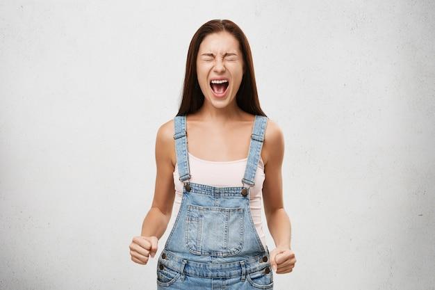 Агрессия, негативная человеческая реакция и отношение. внутренний выстрел разгневанной подчеркнутой молодой женщины, кричащей вслух с широко открытым ртом, закрытыми глазами и сжатыми кулаками, с безумным и яростным взглядом Бесплатные Фотографии