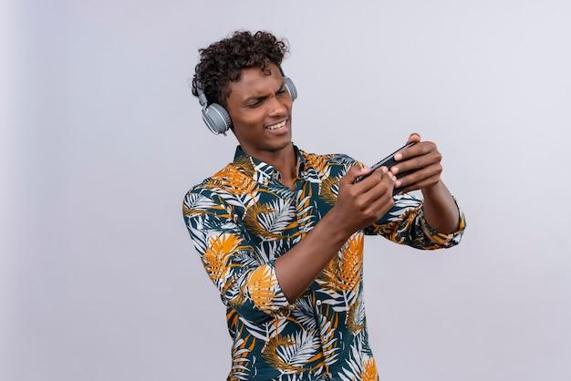 Агрессивный и злой красивый темнокожий мужчина с вьющимися волосами в рубашке с принтом листьев в наушниках играет с мобильным телефоном Бесплатные Фотографии