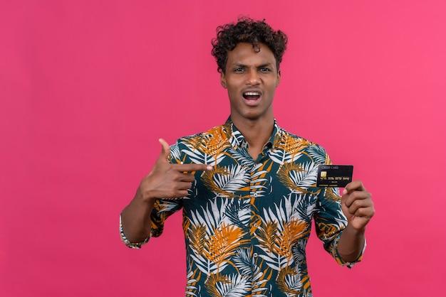 Агрессивный и злой молодой темнокожий мужчина с кудрявыми волосами в рубашке с принтом листьев указывает на кредитную карту Бесплатные Фотографии
