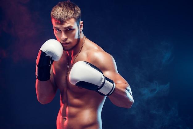Aggressive shirtless boxer on grey background. Premium Photo