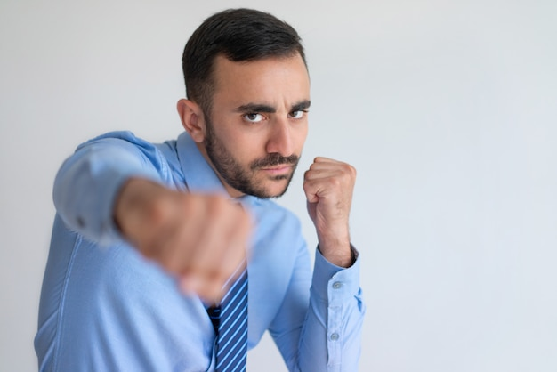 Aggressive young bearded businessman punching camera Free Photo