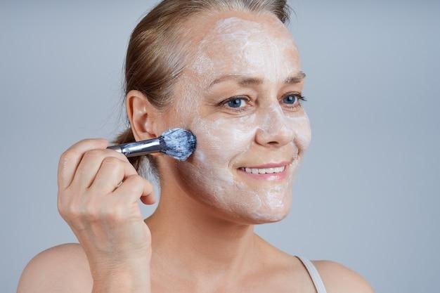 年配の女性は、ブラシで顔に化粧用マスクを適用します。高齢者のスキンケアに直面します。 Premium写真