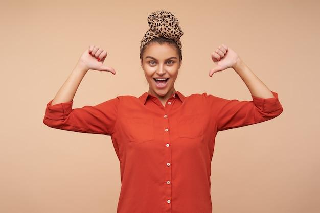 Agitato giovane attraente donna bruna dagli occhi verdi con fascia che sfoglia con gioia su se stessa mentre guarda davanti con un ampio sorriso, isolato sopra il muro beige Foto Gratuite
