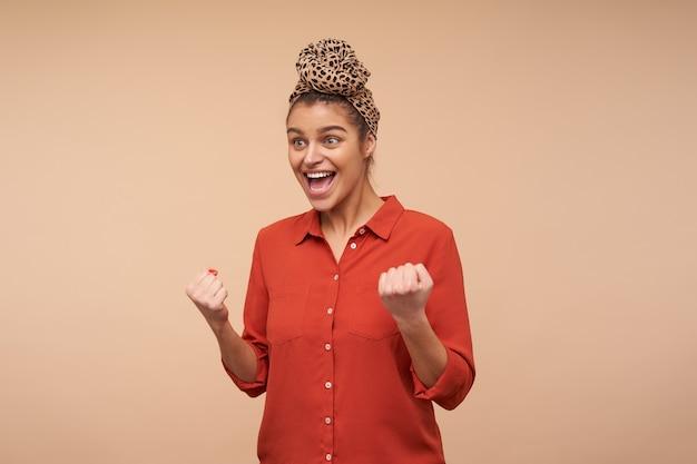 Agitato giovane donna dai capelli castani che indossa la fascia in nodo mentre posa sul muro beige, alzando eccitata le mani e urlando felicemente con la bocca larga aperta Foto Gratuite