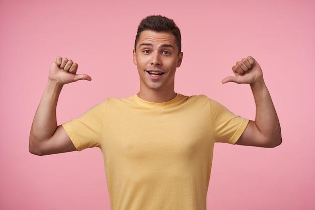 Agitato giovane bella bruna dagli occhi marroni maschio guardando allegramente in telecamera mentre mostra su se stesso con le mani alzate, isolate su sfondo rosa Foto Gratuite