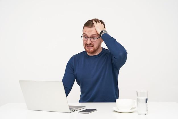 흰색 배경 위에 앉아있는 동안 예기치 않은 뉴스를 읽고 자신의 노트북에서 놀랍게도 자신의 머리를 구겨진 안경에 흥분된 젊은 예쁜 수염 남성 무료 사진