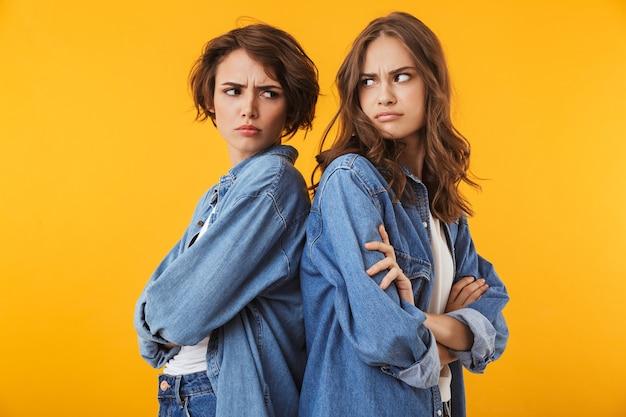 Агрессивные недовольные подруги молодых женщин изолированы на желтой стене  ссоры.   Премиум Фото