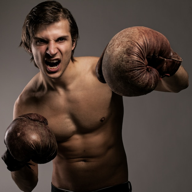 Agressive guy in a boxing gloves Free Photo